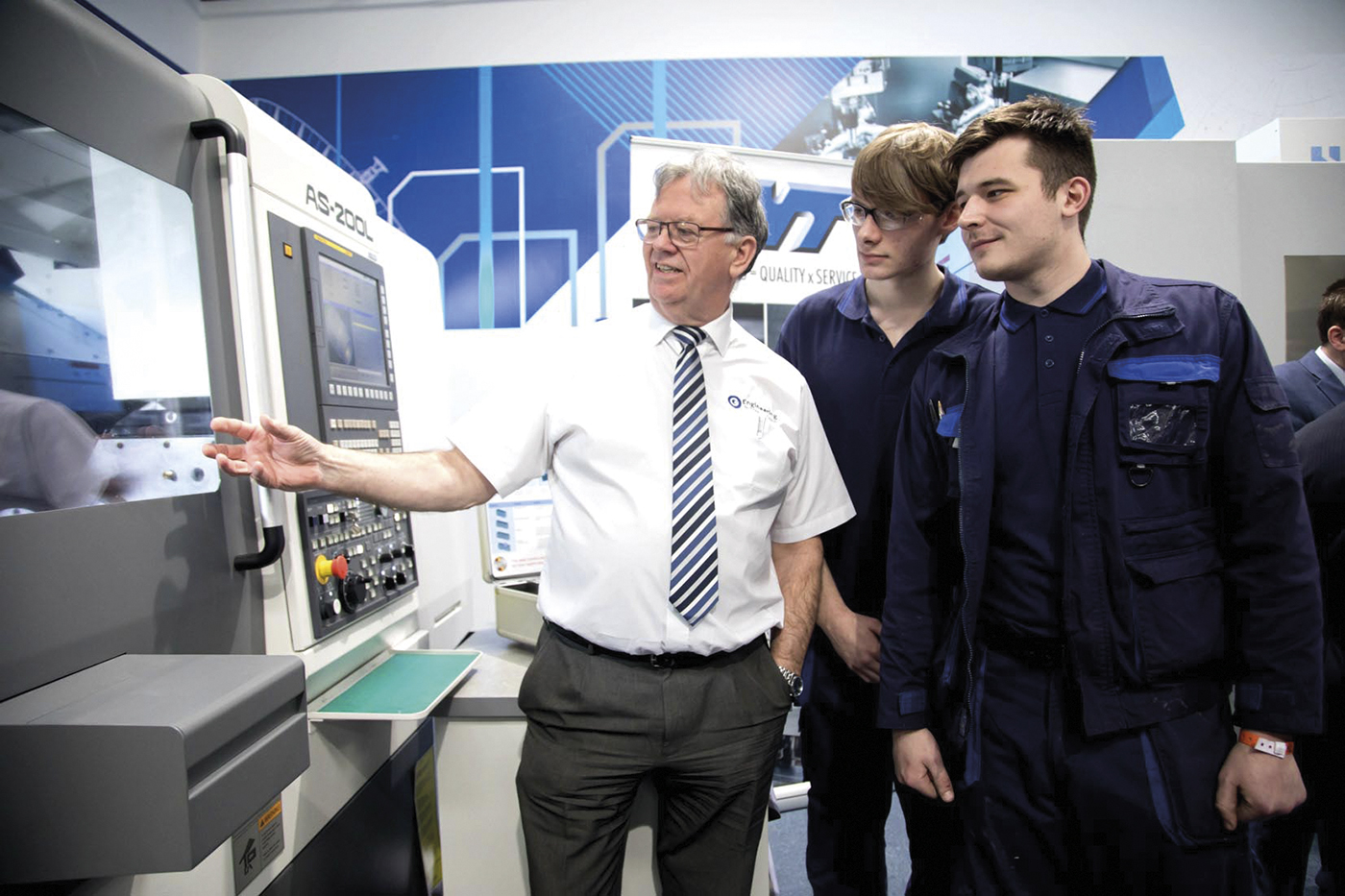 students with teacher looking at technical equipment