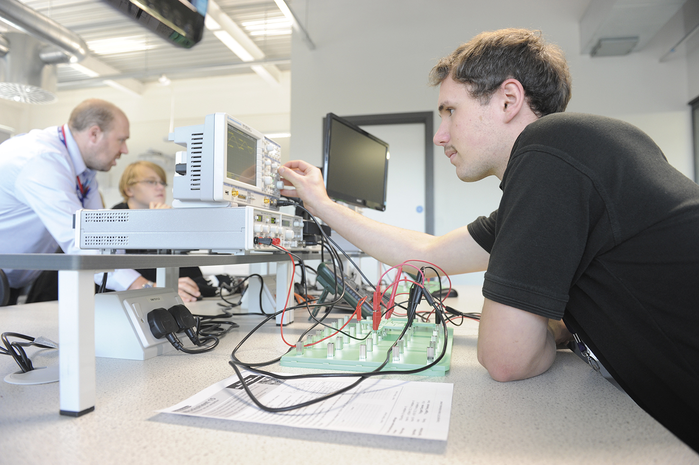 student in classroom looking at technical equipment