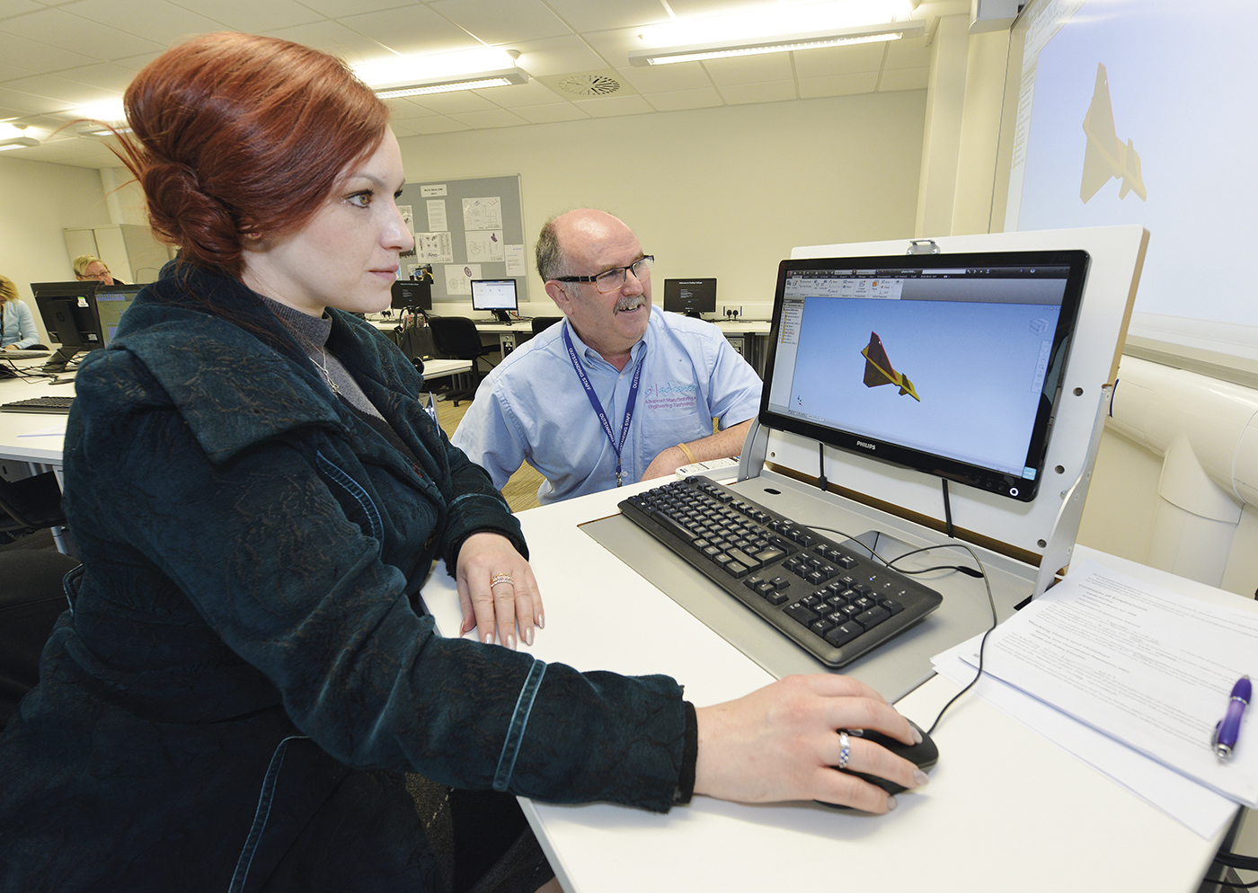 Student and teacher rendering a 3D model on computer in classroom